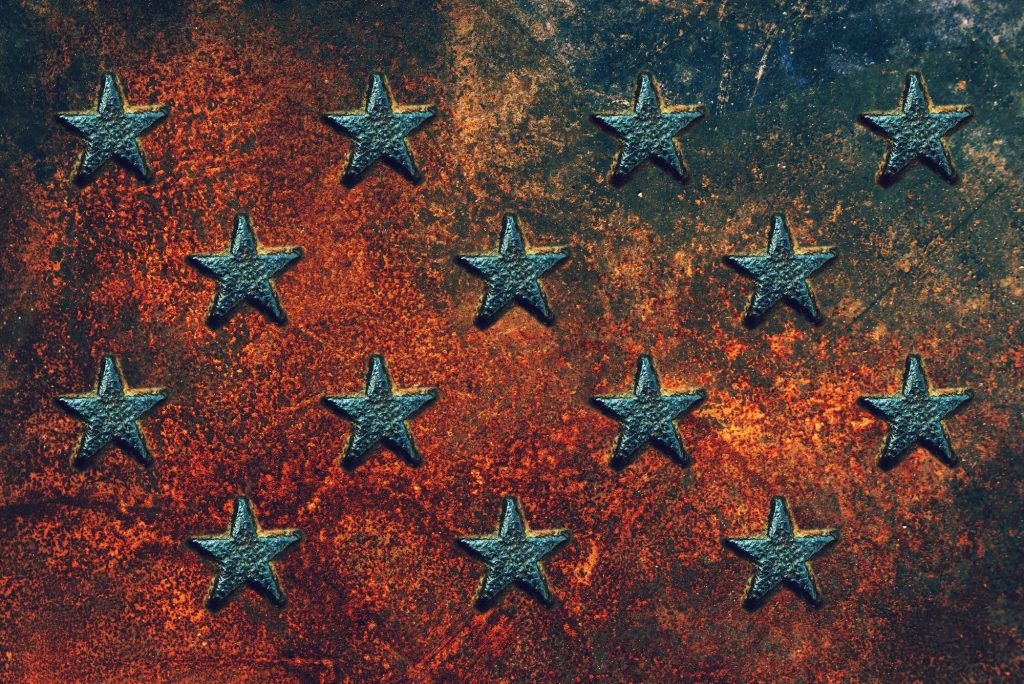 Embossed USA star shapes on rusty metal surface