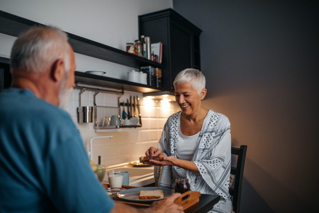 Older people eating in kitchen