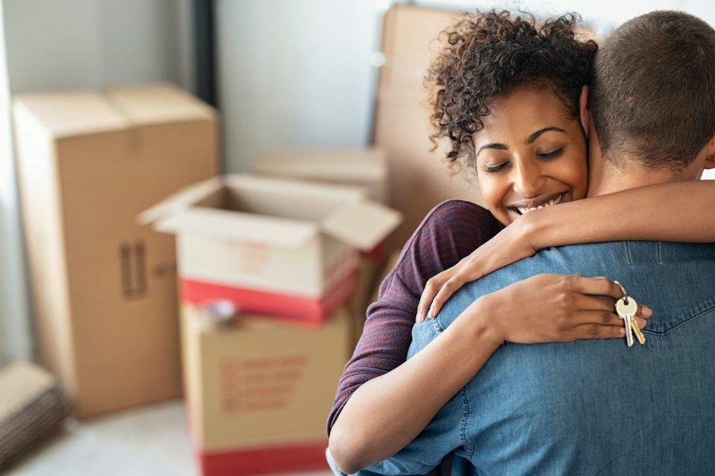 Woman hugging man and holding home keys